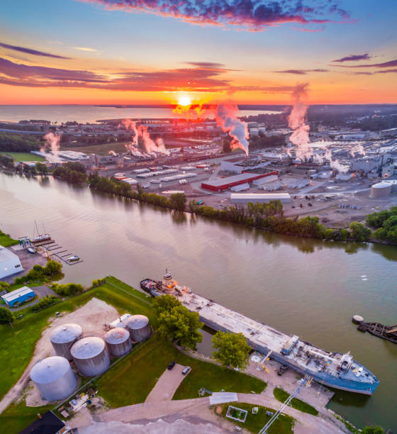 sunrise over industrial riverfront, with ship and factories, aerial view. - green bay wisconsin stock photos and pictures