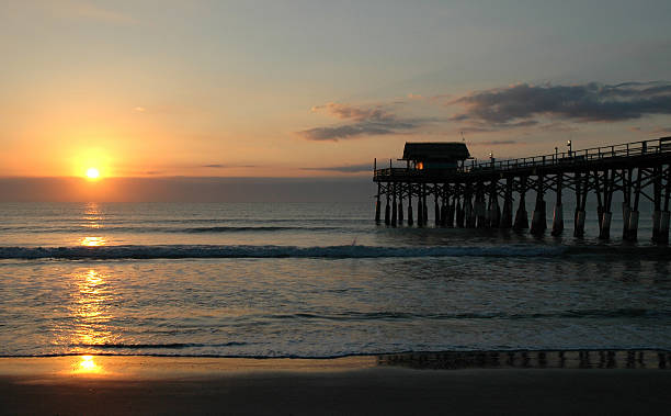 Sunrise over ocean at Cocoa Beach Pier in Florida stock photo