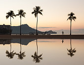 Sunrise in Waikiki with Diamond Head reflected in calm waters of pond as walkers walk along the beach