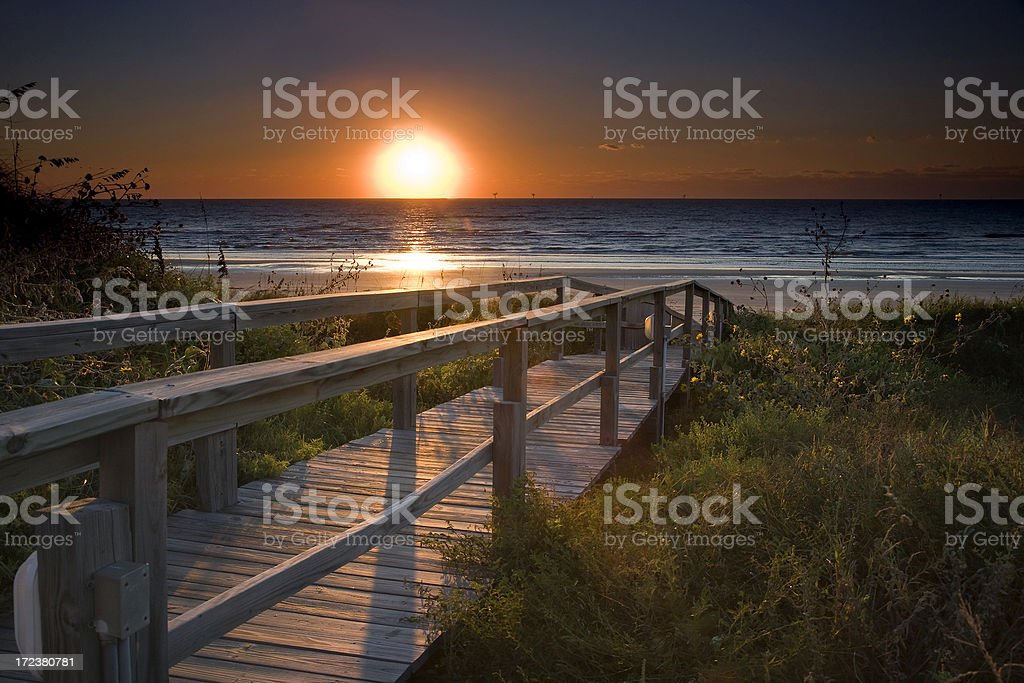 sunrise over pier and beach royalty-free stock photo