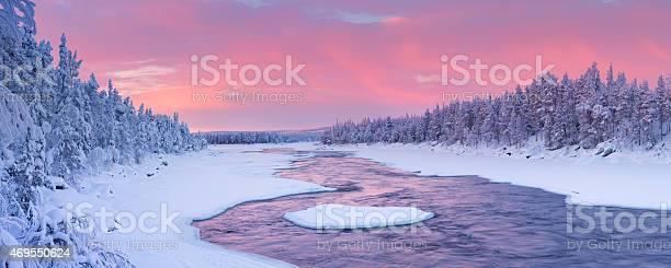 Photo of Sunrise over river rapids in a winter landscape, Finnish Lapland
