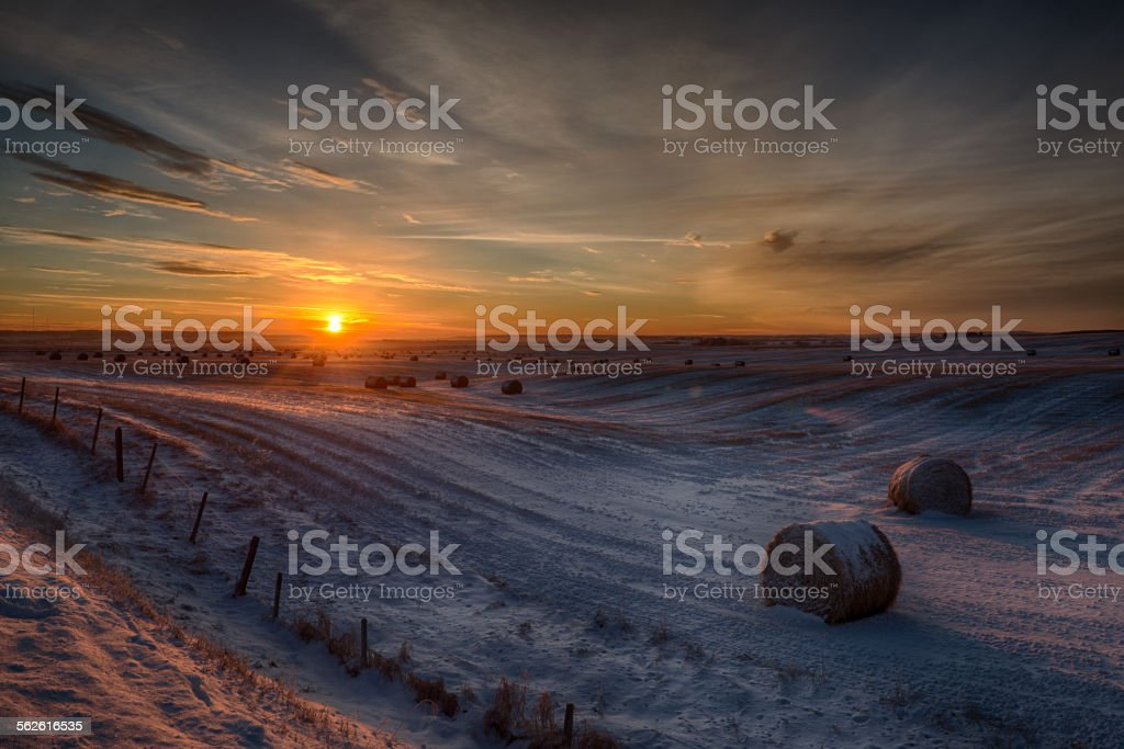 Sunrise over rural fields and hay bales, snow stock photo