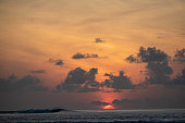 The sun peeks over the horizon in the tropics