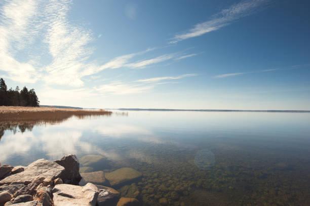 Sol uppgång över stilla vatten på en sjö i Sverige bildbanksfoto