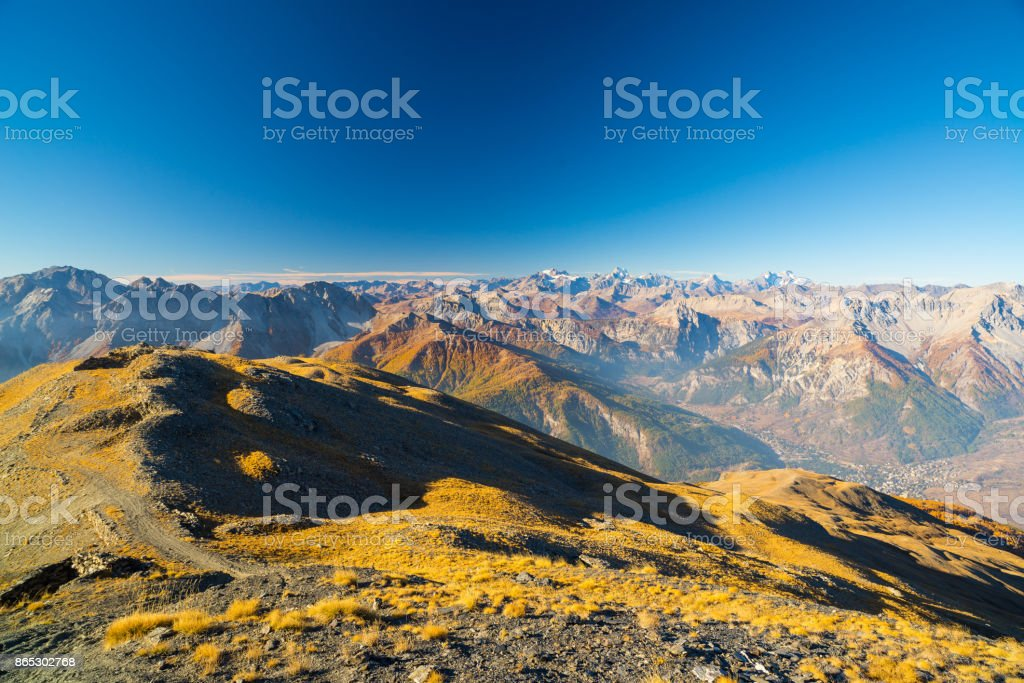Sunrise over the Alps, the Massif des Ecrins (4101 m) national park with glaciers, France. Clear blue sky, autumn colors, expansive view from Bardonecchia, Italy. stock photo