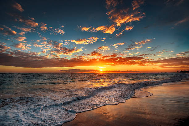 sunrise over the beach - atmospheric mood stock photos and pictures