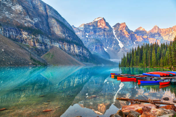 Sunrise Over the Canadian Rockies at Moraine Lake in Canada Sunrise over the Valley of the Ten Peaks with canoes on the glacier-fed, turquoise colored Moraine Lake in the Canadian Rockies. valley of the ten peaks stock pictures, royalty-free photos & images