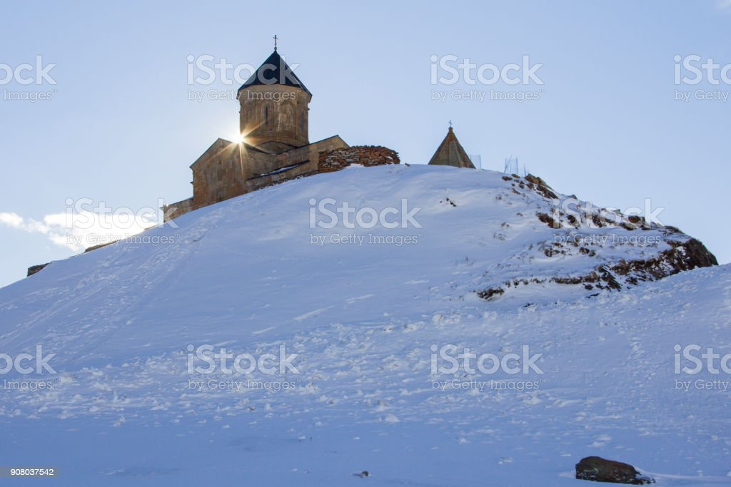 Sunrise over the Church of the Holy Trinity near the village of Gergeti, Georgia. stock photo