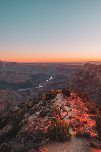 A viewpoint of the majestic glacial carved Grand Canyon and the Colorado River during sunrise or sunset at Grand Canyon National Park in Arizona, USA.