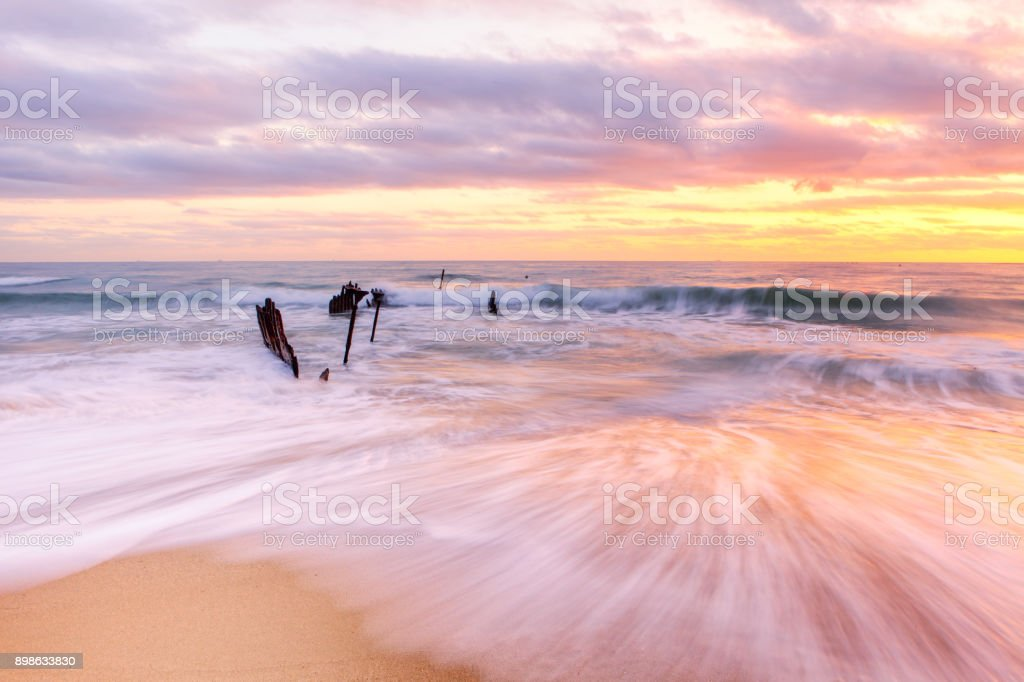Sunrise over the Dicky Beach Shipwreck on Queensland's Sunshine Coast in Australia stock photo