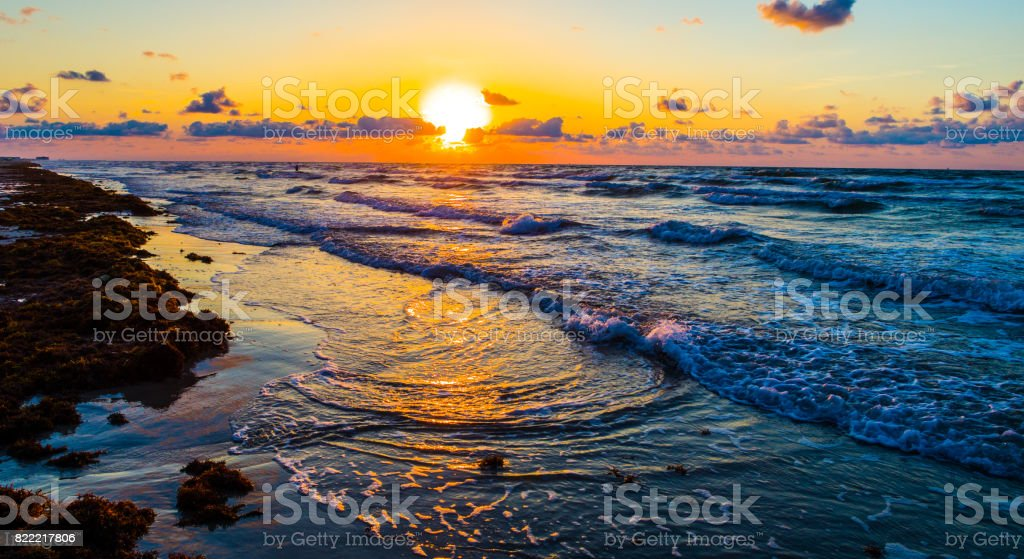 Sunrise over the Ocean on Padre Island as waves crash on the the shoreline stock photo