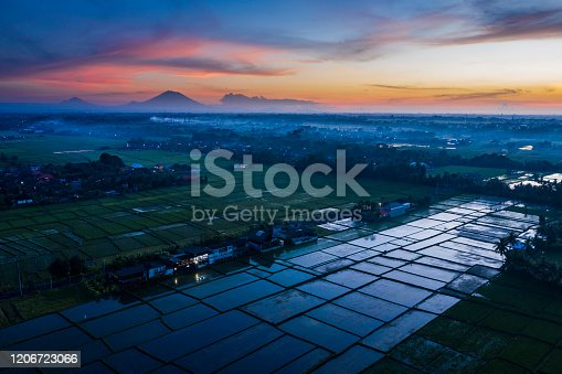 Aerial landscape taken by drone of a colorful sunrise in Bali with rice paddy field and the Mount Agung sitting on the horizon