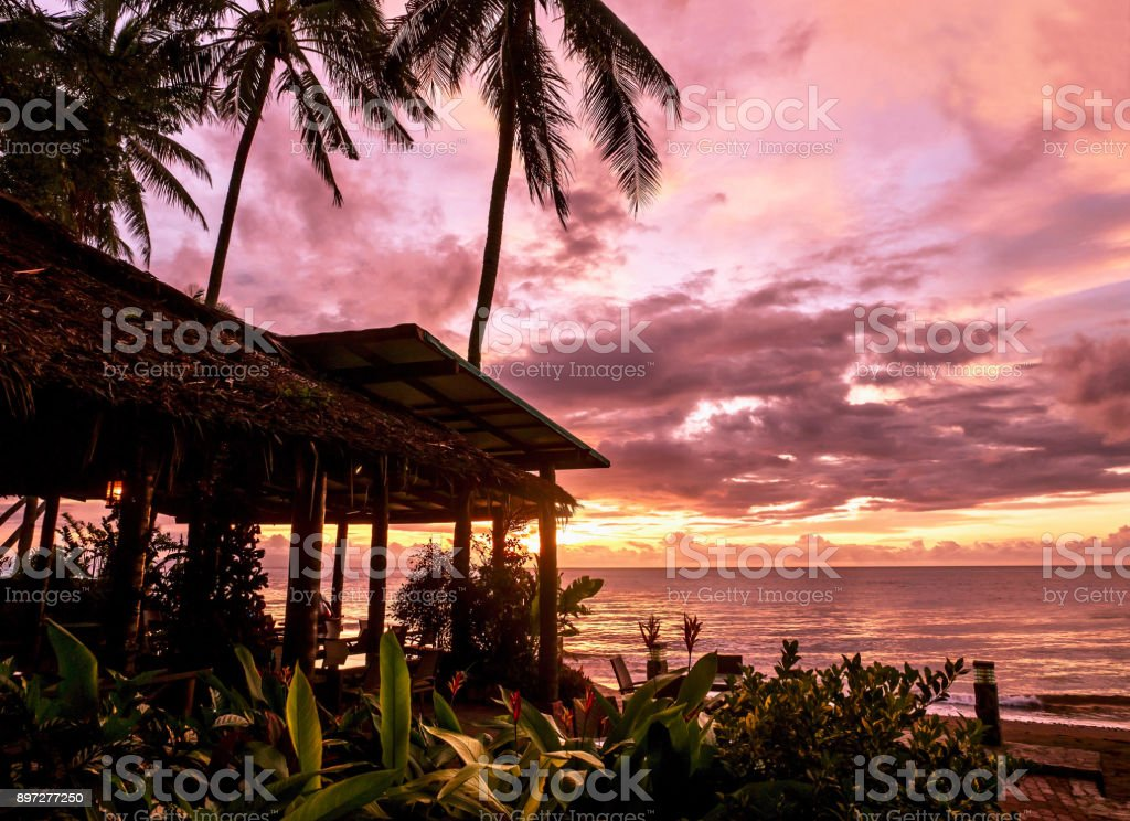 Sunrise over the sea at a romantic, rustic beach resort on a tropical island, with palm trees and hotel restaurant in silhouette against the magenta sky. stock photo