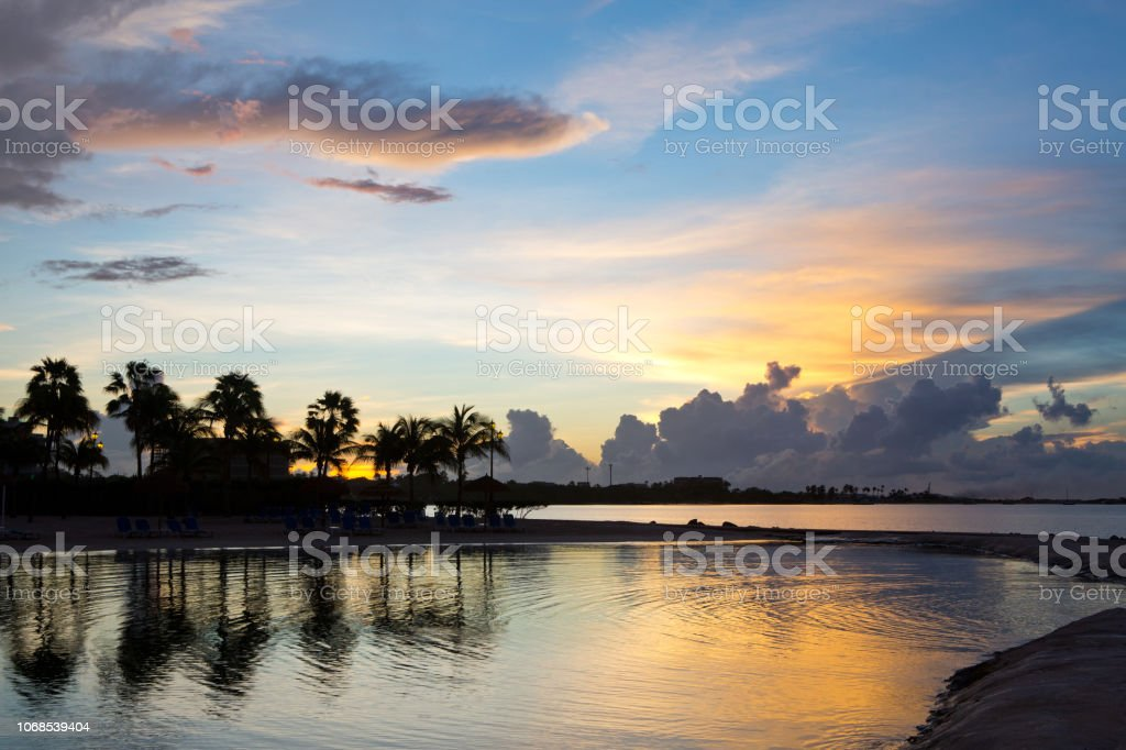 Sunrise over the sea with palm tree reflections stock photo