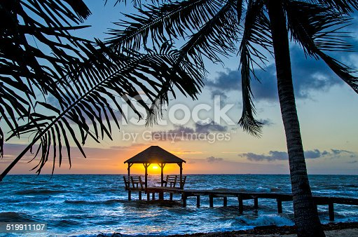 A palapa at sunrise on the end of a pier in Placencia, Belize.