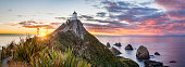 Panoramic view of sunrise at Nugget Point, or The Nuggets, Catlins, Otago, in New Zealand's South Island.