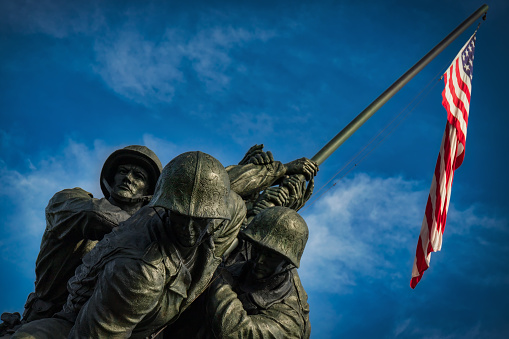 Arlington, Virginia / United States - September 7, 2018: The US flag silently hangs over the US Marine Corps War Memorial designed by sculptor Felix de Weldon and architect Horace W. Peaslee which was unveiled on November 10, 1954.