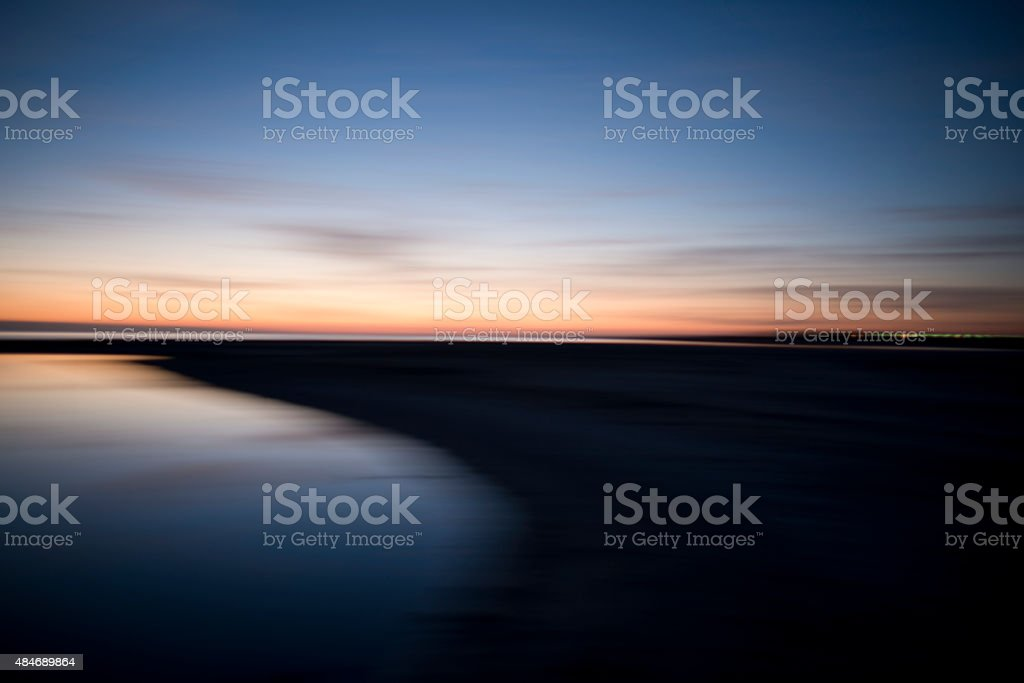 Sunrise Sunrise over water with distant city lights 2015 Stock Photo