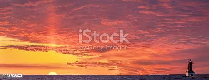 Sunrise pillar of light in dramatic red sky, with lighthouse. The light pillar is a common yet stunning site in Northern climates, it is caused by cold weather and ice crystals in the atmosphere.