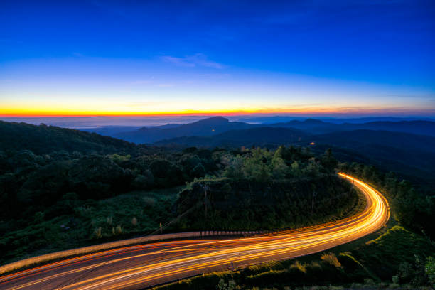 Sunrise scence of car light trail to the top with curve of road at Doi Inthanon National park in Chiang Mai Province, Thailand. stock photo