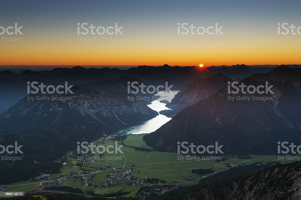 sunrise scene in austrian mountains with view to lake plansee stock photo