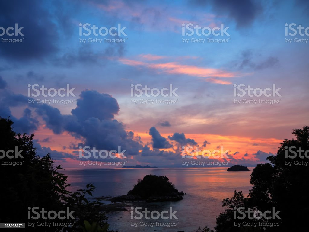 Sunrise sea view with small island and colorful sky through green tree leaves silhouette, Lipe island, Thailand foto stock royalty-free