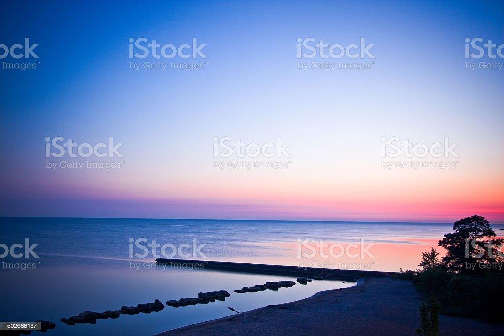Sunrise Shoreline of Lake with Pier stock photo