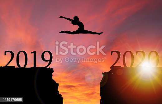 istock Sunrise Silhouette of Girl Leaping Over Cliff Toward New Year 2020 1139179686