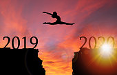 Sunrise silhouette of girl leaping from 2019 toward 2020 over cliff. Concept of boldness, courage, or leap of faith toward a new year.