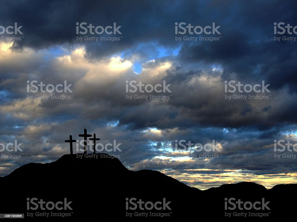 A depiction of the three crosses of Calvary. The darkened landscape...