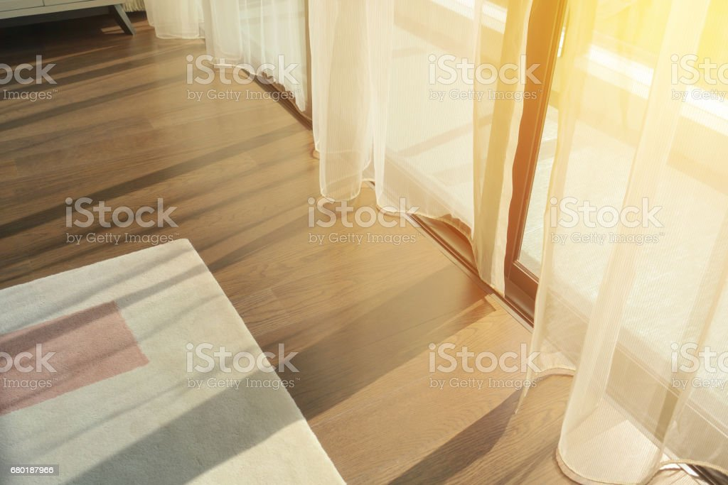 sunrise through transparent curtains of a window in the morning stock photo