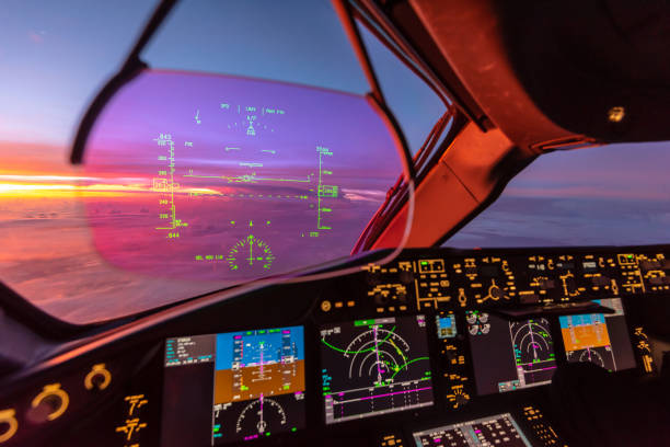 Sunrise view from modern aircraft cockpit with Heads up Display and flight instruments stock photo