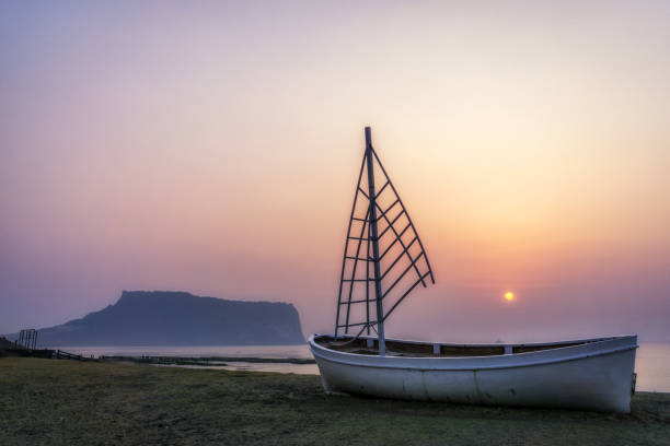 sunrise view sailboat gwangchigi beach sunrise over a sailboat in gwangchigi beach with the view of seongsan ilchulbong in jeju island, south korea seogwipo stock pictures, royalty-free photos & images