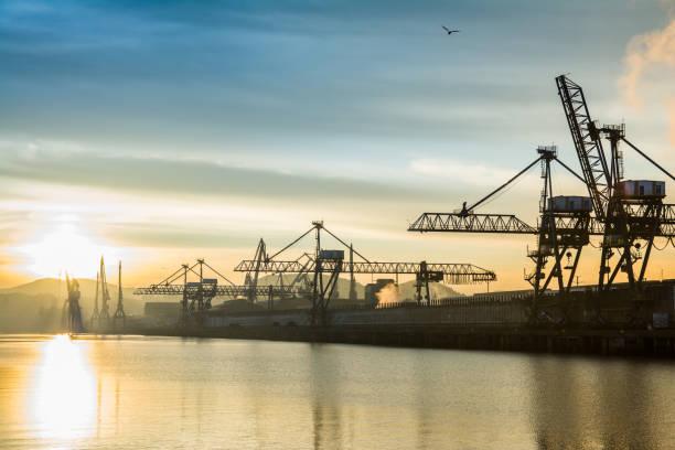 sunrise view to Bilbao industrial cranes, spain stock photo