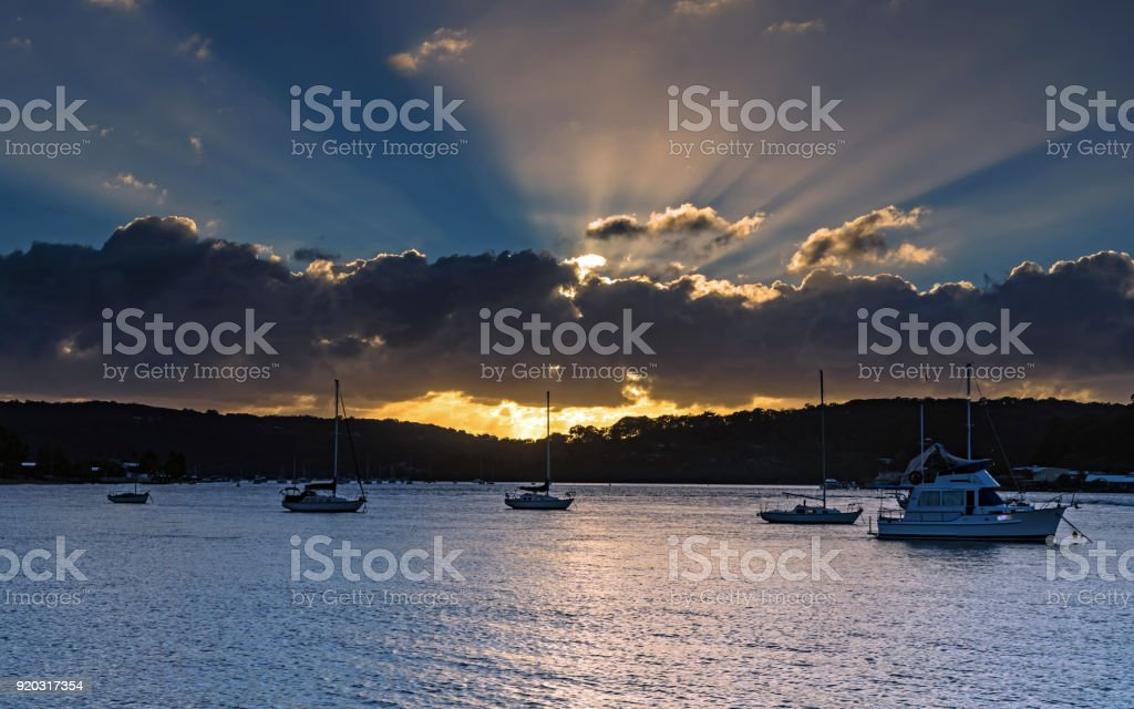 Sunrise Waterscape with Sun Rays and Boats stock photo