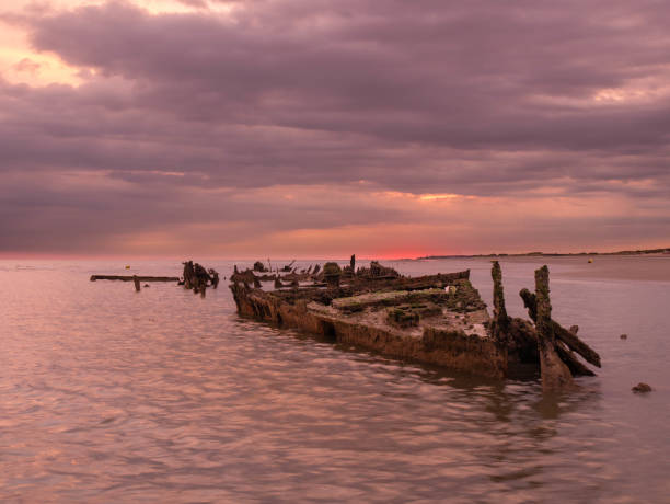 Sunrise with a sunken shipwreck from World War II close to the beach At low tide this shipwreck is visible close to Bray-Dunes in France sunken stock pictures, royalty-free photos & images