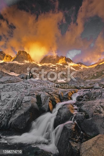 Sunrise with clouds over the Minaret Range of the Sierra Navada Mountains and a small stream flowing down the foreground. Ansel Adams Wilderness Area, California.