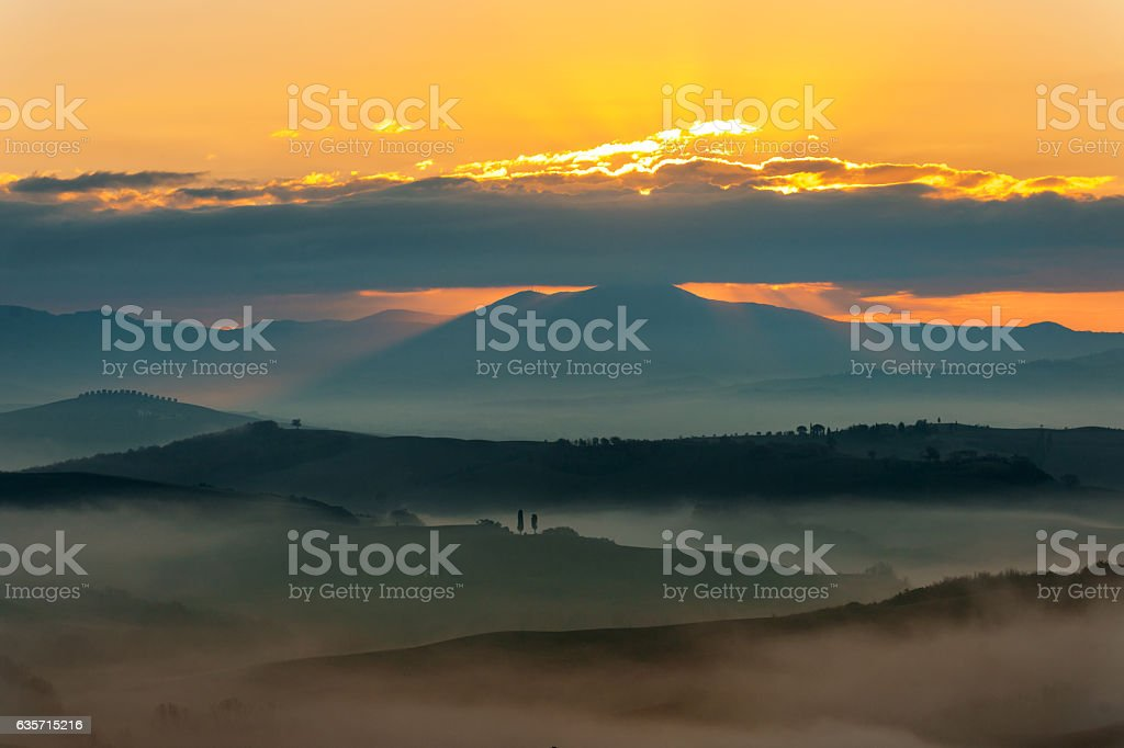 Sunrise with rays over the Misty valleys in Tuscany,Italy. royalty-free stock photo