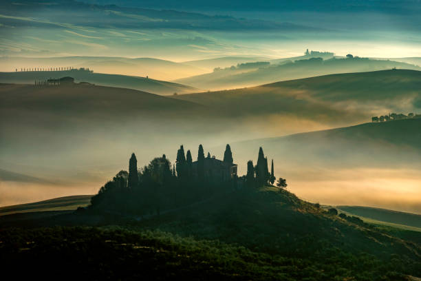 Sunrise with rays over the misty valleys in Tuscany,Italy,Europe stock photo