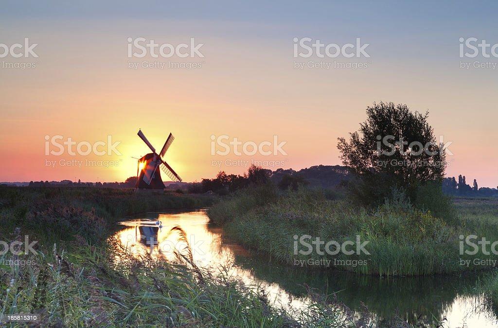 sunrise with sun behind Dutch windmill royalty-free stock photo