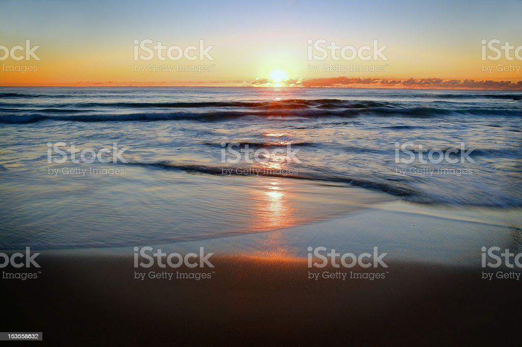 Sunrise with waves on beach stock photo