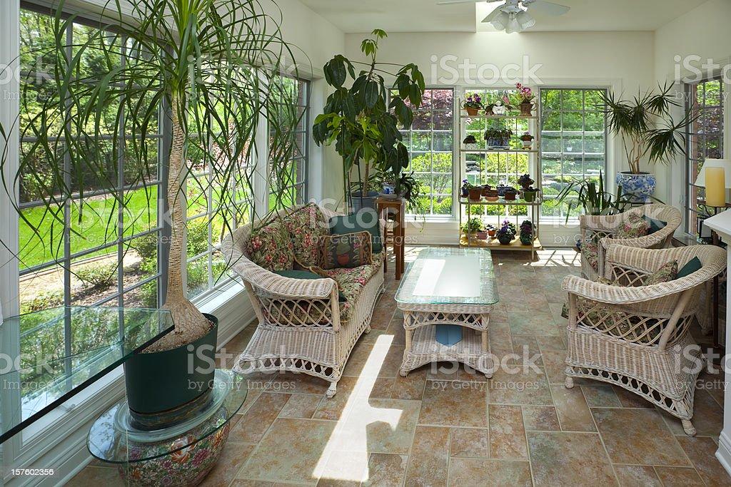 Solarium serra interni con mobili in vimini casual piante