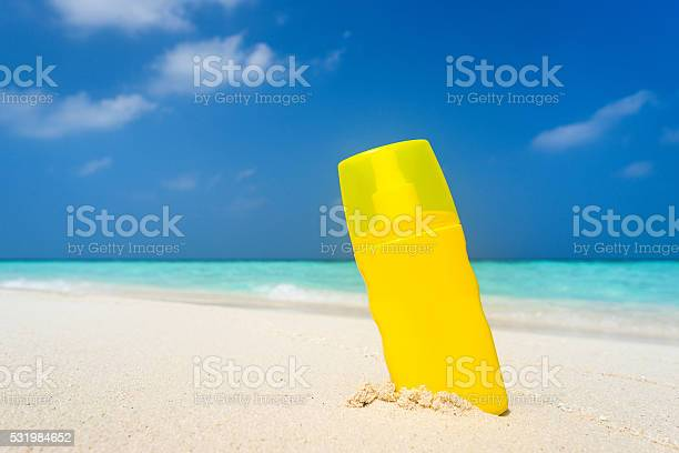 Sunscreen Cream Bottle On The Beach Stock Photo - Download Image Now