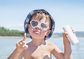 Sunscreen is on hipster boy face before tanning during summer holiday on beach. Caucasian child (kid) have sunglasses, hat and holding container of suntan lotion (not far from Trieste, Italy). Outdoor, close up.