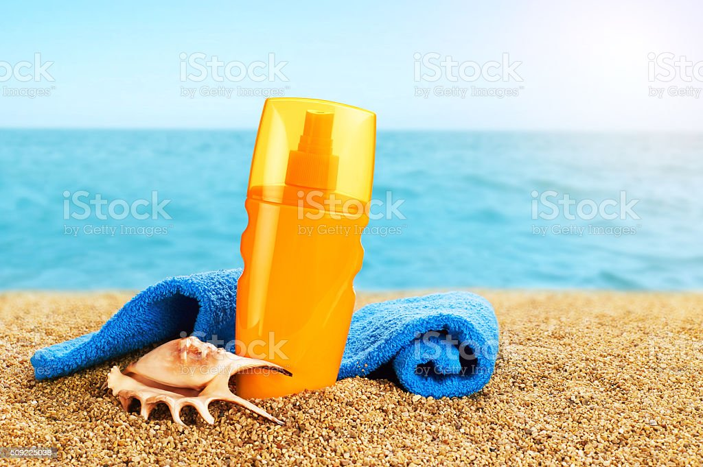 Sunscreen spray and towel on the beach. stock photo