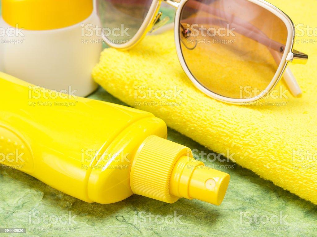 Sunscreen spray bottle, jar of sun cream, towel and sunglasses stock photo