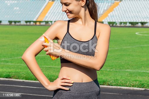 Sunscreen sunblock. Woman in a sportswear putting solar cream on shoulder on beautiful summer day. Sporty woman applying sunscreen on sport stadium. Sports and healthy concept.