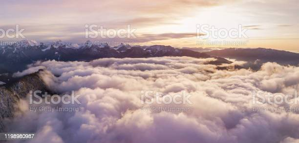 Photo of sunset above clouds in Alps mountains, beautiful cloudscape panorama