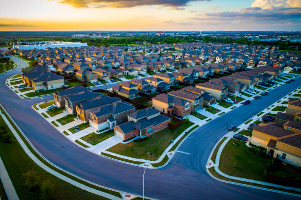 sunset above suburb aerial drone view high above homes in austin texas - urban sprawl stock photos and pictures