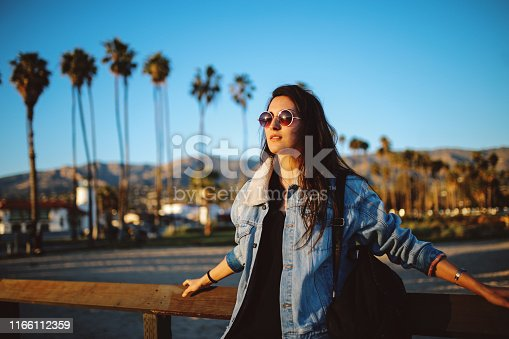 Beautiful sunset above the Santa Barbara boardwalk. Portrait of a brunette woman, enjoying the ocean view. She is wearing fashionable, retro styled streetwear, a denim jacket and sunglasses, under the California sunshine.